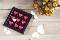 Coeurs rouges de chocolat en boîte et fleurs sur la table en bois Photographie stock libre de droits