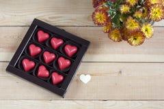 Coeurs rouges de chocolat en boîte et fleurs sur la table en bois Images stock