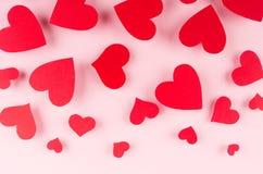 Coeurs rouges de papier tombant sur le fond rose mou de couleur Concept de Saint Valentin pour la conception Image libre de droits