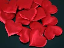 Coeurs rouges de satin sur le noir Images libres de droits