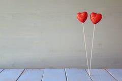 Coeurs rouges de scintillement de couples sur la table en bois Photo libre de droits