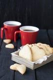 Coeurs rouges de tasse et de biscuit sur un fond noir Images stock