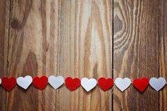 Coeurs rouges et blancs de Ppaper sur la corde à linge sur le backgrou en bois Images stock