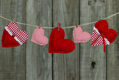 Coeurs rouges et blancs de tissu de pays accrochant sur la corde à linge par la barrière en bois Images stock