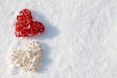 Coeurs rouges et blancs de valentine dans la neige Photos libres de droits