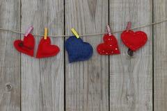 Coeurs rouges et bleus de calicot accrochant sur la corde à linge Photo libre de droits