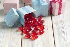 Coeurs rouges et boîte-cadeau colorés sur le fond en bois Image libre de droits