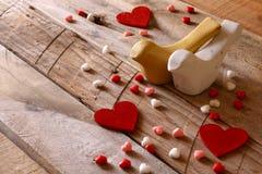 Coeurs rouges et deux oiseaux affectueux sur la table en bois Image libre de droits