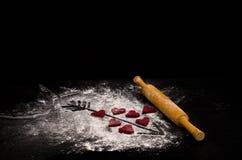 Coeurs rouges faits de la pâte, de la goupille en bois et d'une flèche peinte sur la farine Copyspace Images libres de droits