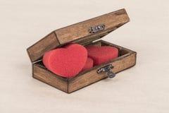Coeurs rouges mous dans une boîte en bois Photos stock