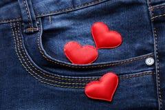 Coeurs rouges sur le backround de jeans Photo stock