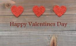 Coeurs rouges sur les coeurs rouges en bois sur le fond en bois de jour de valentines Photo stock