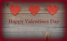 Coeurs rouges sur les coeurs rouges en bois sur le fond en bois de jour de valentines Photographie stock libre de droits