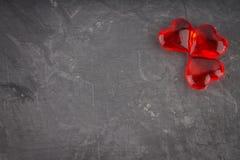 Coeurs rouges sur un fond gris Le symbole du jour des amants Photographie stock libre de droits