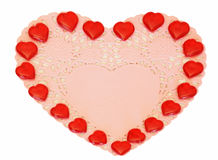 Coeurs rouges sur un napperon rose Photographie stock libre de droits