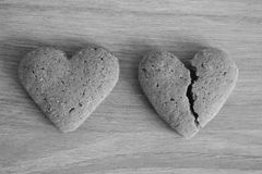 Coeurs sablés cassés et ininterrompus sur le fond en bois noir et blanc en tant que fond malheureux d'amour Photographie stock libre de droits