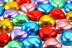 Coeurs sous emballage souple colorés de chocolat Photos stock