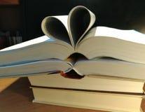 Coeurs sur des livres sur un fond noir images stock