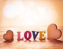 Coeurs sur le fond en bois avec amour de lettres Photographie stock libre de droits