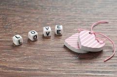 Coeurs sur le panneau en bois avec amour de lettres Image libre de droits