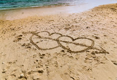 Coeurs sur le sable près de l'océan Photos stock