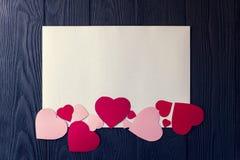 Coeurs sur une feuille de papier blanche, fond foncé Photos libres de droits