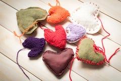 Coeurs tricotés colorés sur la lumière, panneaux en bois Photographie stock