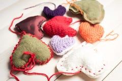 Coeurs tricotés colorés sur la lumière, panneaux en bois Photo stock