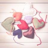 Coeurs tricotés colorés sur la lumière, panneaux en bois Image libre de droits