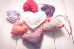 Coeurs tricotés colorés sur la lumière, panneaux en bois Photos libres de droits