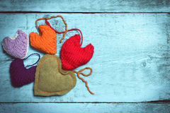 Coeurs tricotés colorés sur les conseils bleu-clair Photos stock