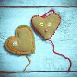 Coeurs tricotés colorés sur les conseils bleu-clair Photographie stock
