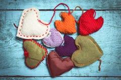 Coeurs tricotés colorés sur les conseils bleu-clair Image libre de droits