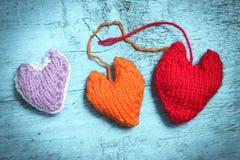 Coeurs tricotés colorés sur les conseils bleu-clair Images libres de droits