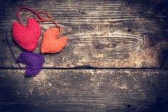 Coeurs tricotés colorés sur les vieux conseils foncés Photographie stock