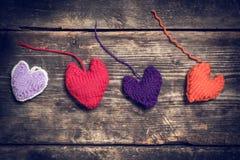 Coeurs tricotés colorés sur les vieux conseils foncés Image stock