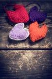 Coeurs tricotés colorés sur les vieux conseils foncés Photos stock
