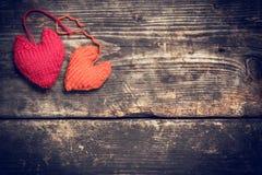 Coeurs tricotés colorés sur les vieux conseils foncés Photo stock