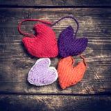 Coeurs tricotés colorés sur les vieux conseils foncés Image libre de droits
