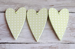 Coeurs vert pâles pointillés sur le fond en bois Image stock