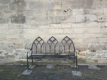Solitary bench against old stone wall royalty free stock image