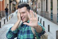 Cofa się mężczyzny zakrywa jego twarz podczas gdy ono uśmiecha się fotografia royalty free