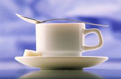 Cofe, food. Cup of coffee on  plate with dessertspoon and two slices of sugar on  dark blue background Stock Photo