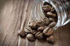 Cofee beans pulled out of glass jar. Close-up royalty free stock image