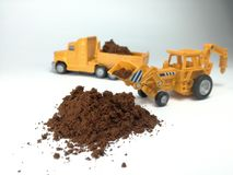 Cofee or cacao powder. Yellow excavator and truck working on cofee or cacao powder. Toys royalty free stock photos