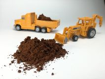 Cofee or cacao powder. Yellow excavator and truck working on cofee or cacao powder. Toys stock images