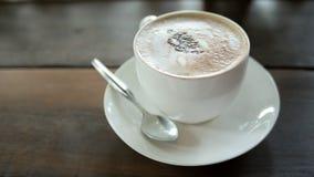 Cofee caliente del mocca en una taza con la cuchara y el plato blanco, colocados en el wo Imagen de archivo libre de regalías