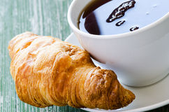 Cofee and croissant on green table Royalty Free Stock Image
