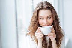 Cofee de consumición atractivo de la mujer joven en casa Imágenes de archivo libres de regalías