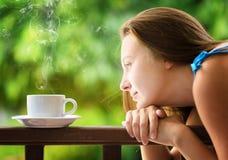Cofee de consumición de la mujer joven en un jardín Fotos de archivo